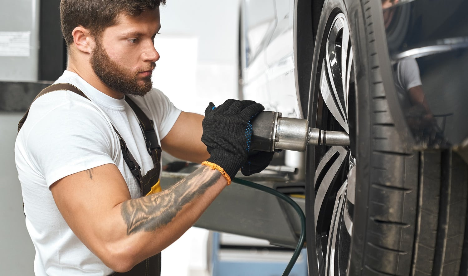 Bearded, brutal mechanic fixing hubcap of auto wheel, using equipment. Muscular man in white t shirt with tattoo on hand wearing in black gloves, working in autoservice.