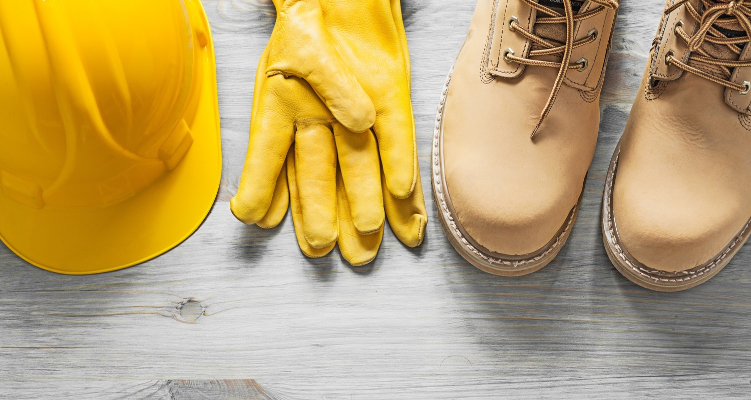 Pair of waterproof boots hard hat leather safety gloves on wooden board construction concept.