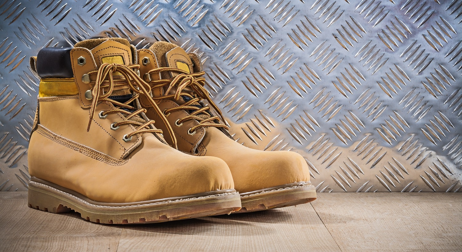 Pair of protective waterproof boots wooden board grooved metal sheet construction concept.