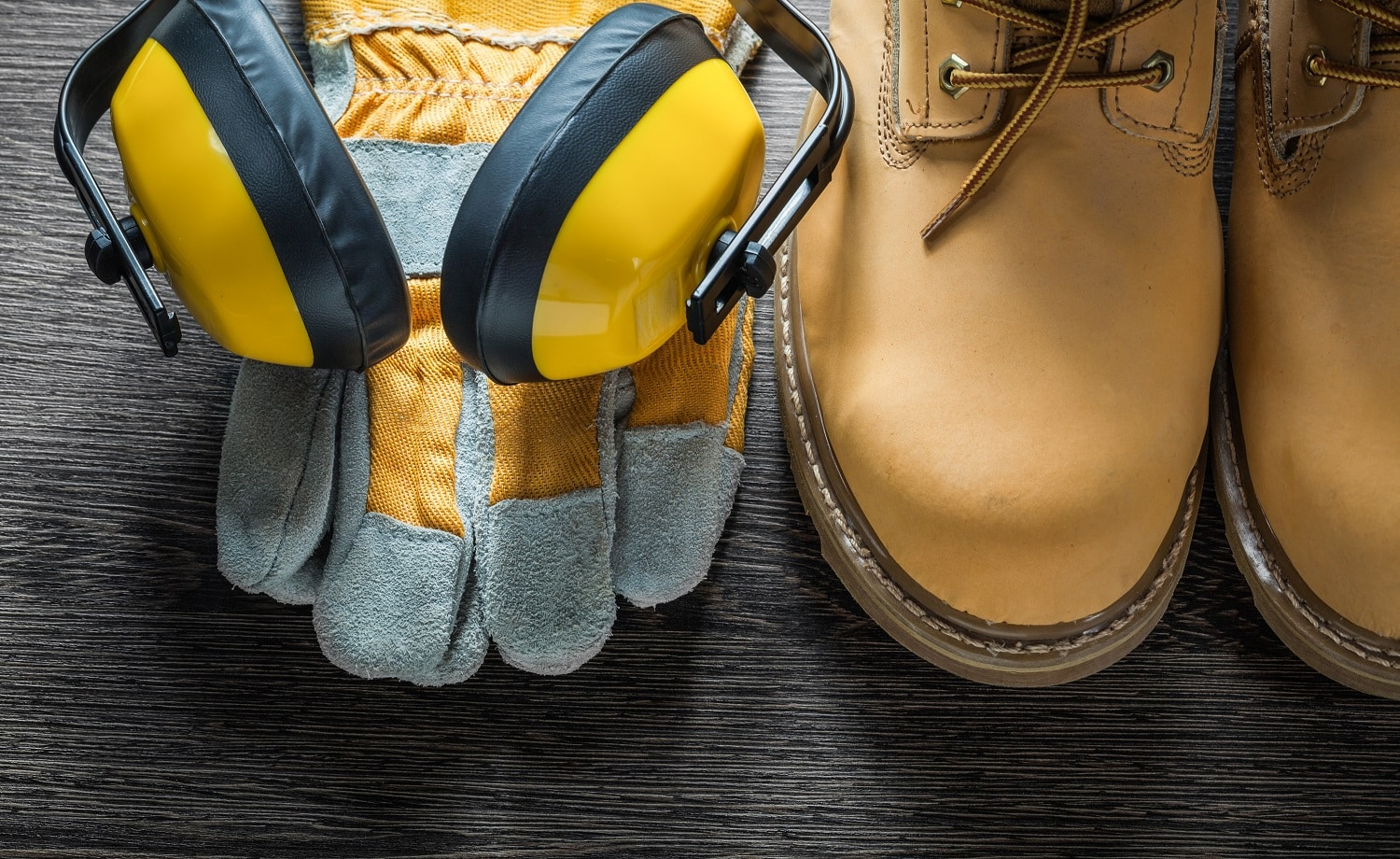 Protective gloves working lace boots ear muffs on wooden board.