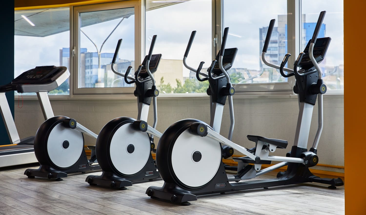 Elliptical trainers standing in a row, gym with large windows, view of the whole city
