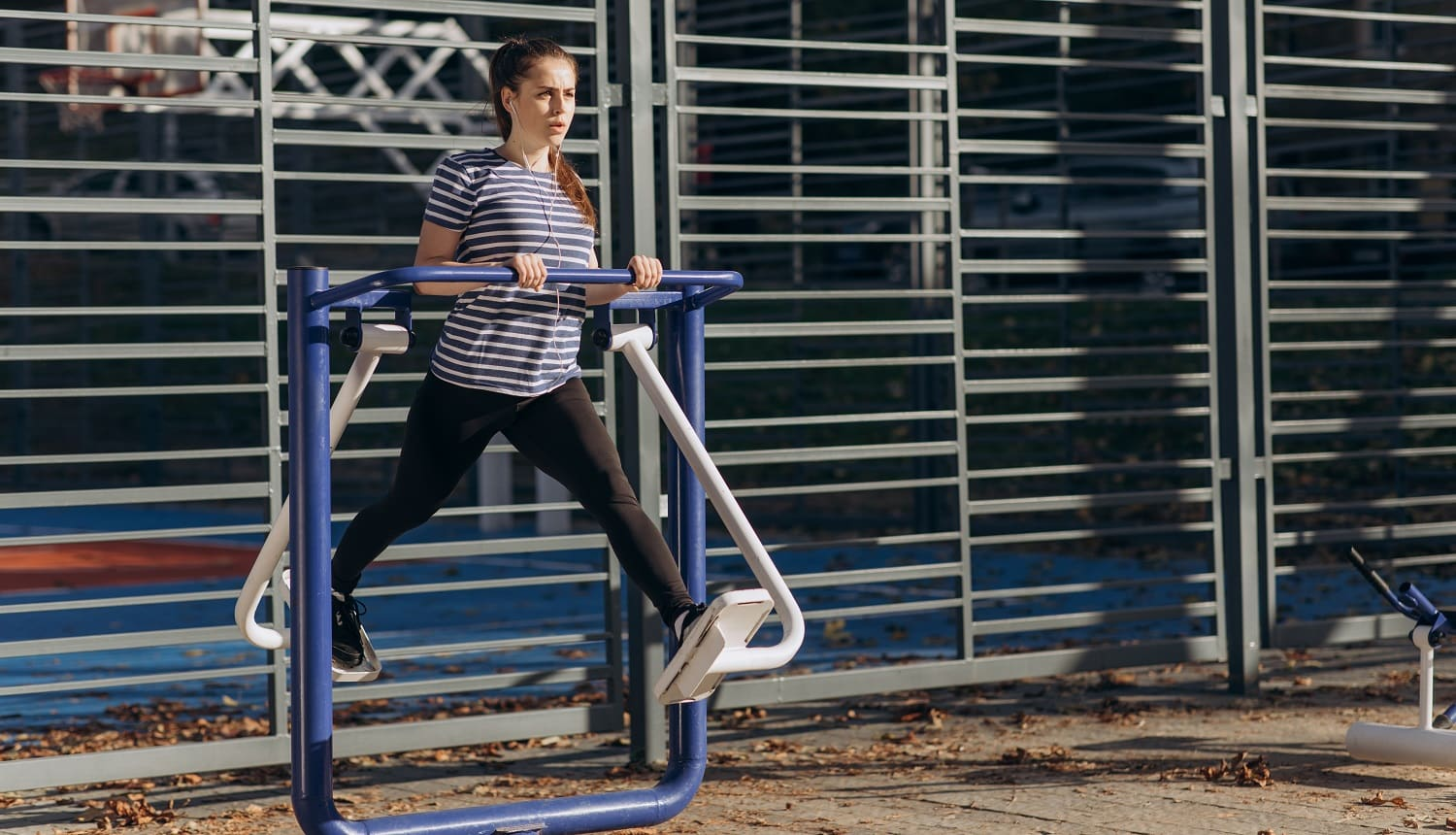 Young sportive woman do walking exercises at outdoor gym, using cross trainer machine. Sunny morning time, girl perform daily fitness workout. Concept of losing weight with exercise for health