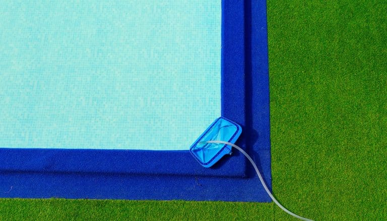 Top view cleaning net at on the edge of the pool is green and blue artificial grass.