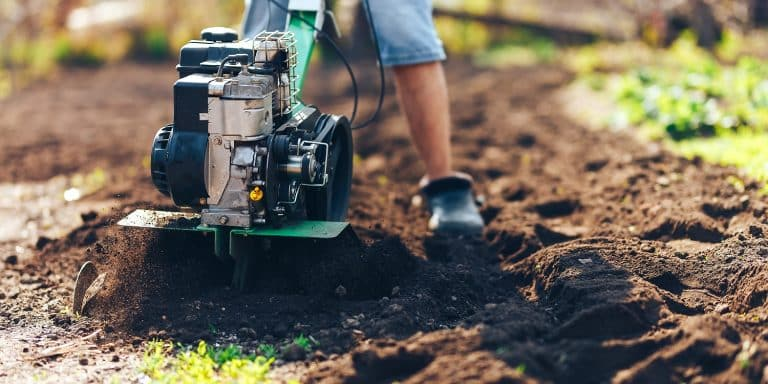 close up photo of gardener cultivate ground soil rototiller , tiller tractor, cutivator, miiling machine, prepare for planting crop, spring. modern farming, technology agriculture.