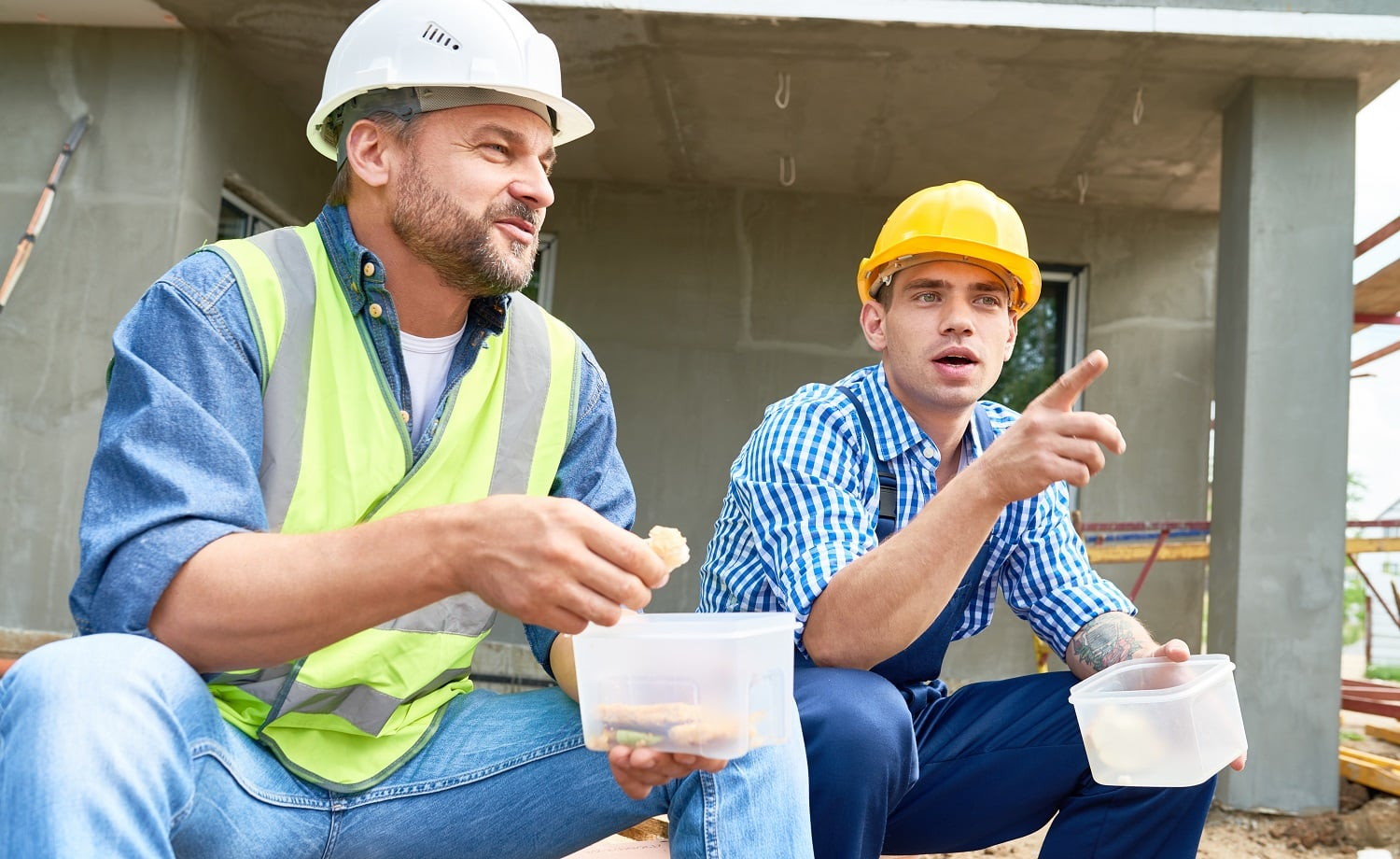 Portrait of two construction workers taking break on site eating lunch out of plastic containers outdoors