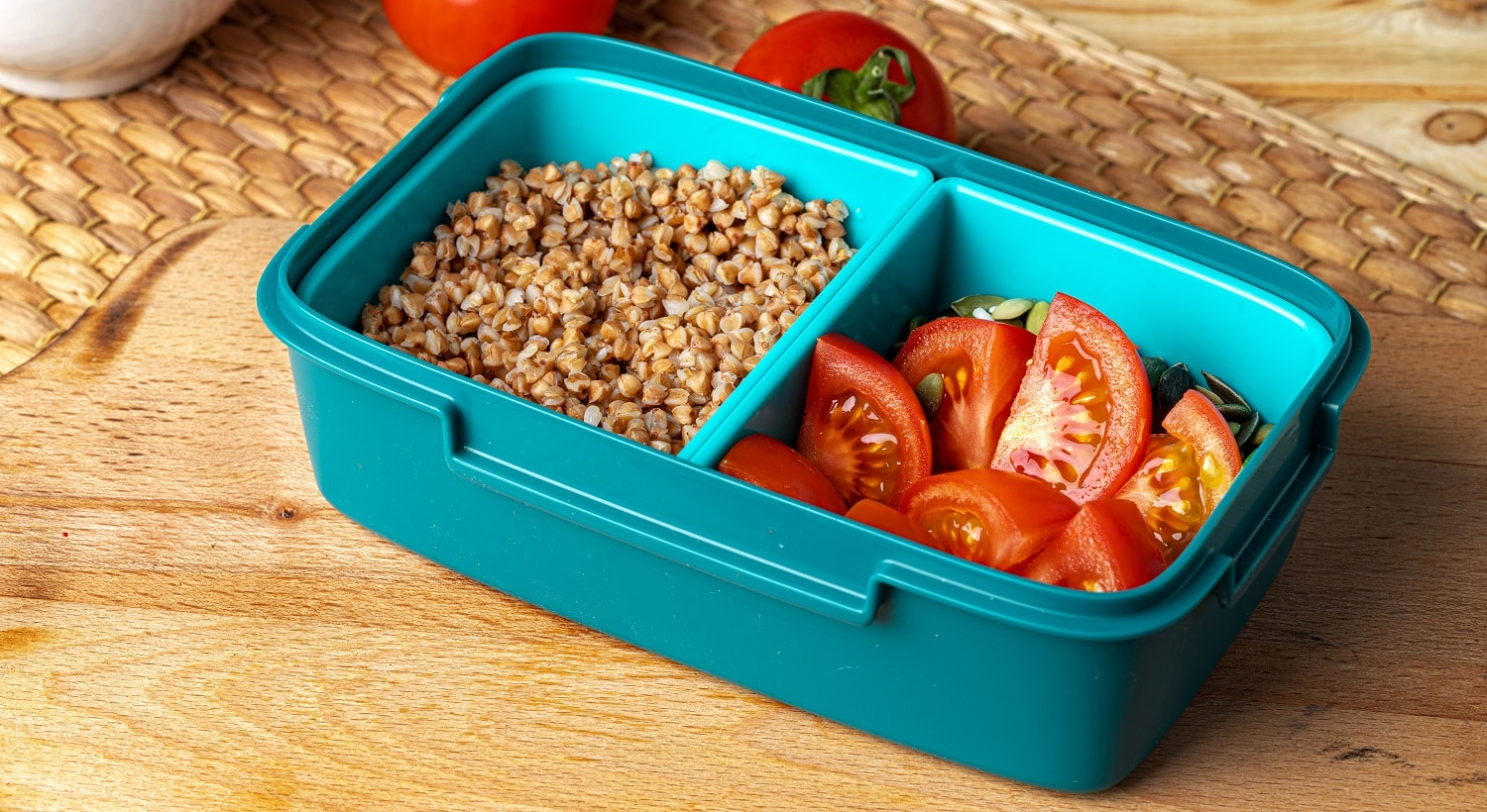 Blue lunch box with buckwheat and tomatoes, healthy eating