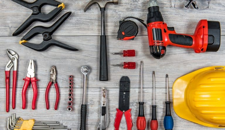 Various construction, DIY hand tools lies in knolling organization on a rustic wooden table, desk or workbench.