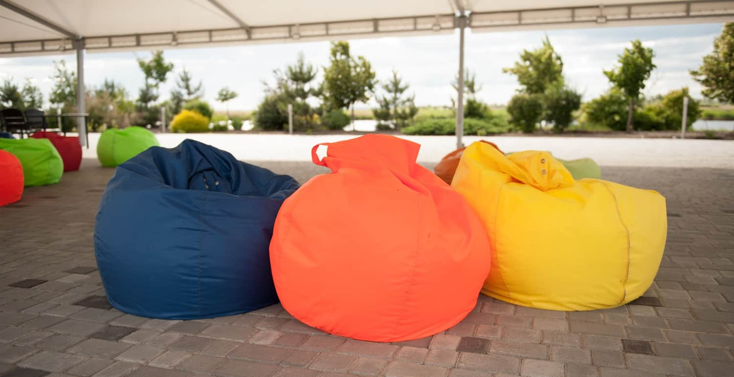 many colorful soft beanbag seats. under a canopy for relaxing
