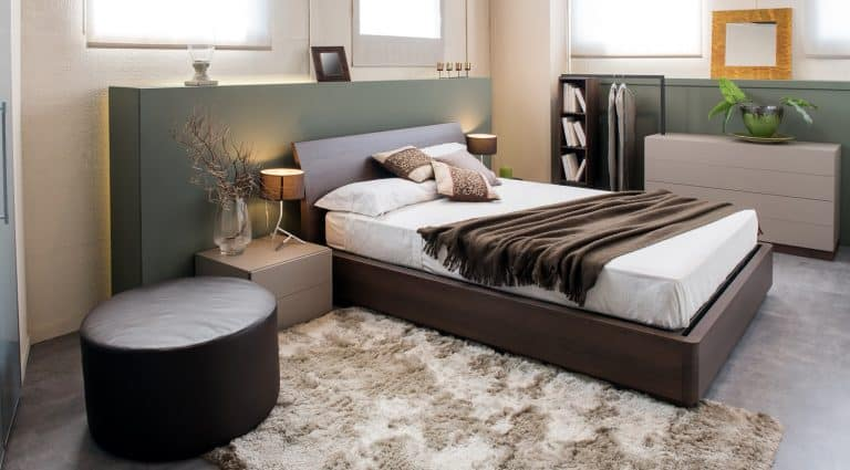 Modern luxury brown monochrome bedroom interior with large headboard above a double beds with cabinets, ottoman and built in wardrobe