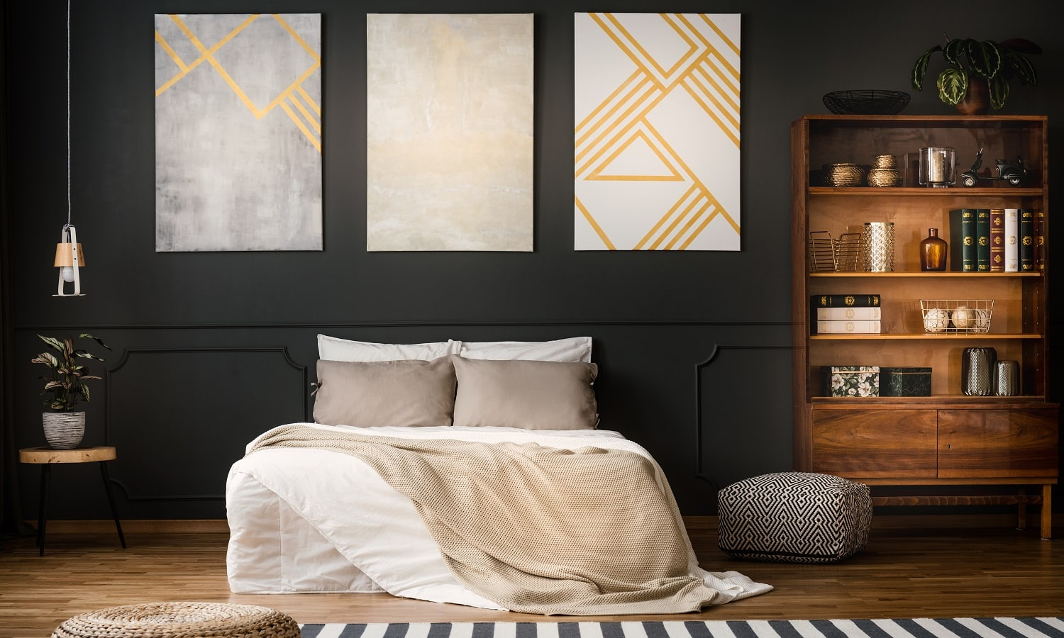 Elegant, wooden, antique bookcase in a dark, modern bedroom interior with a black wall and beige paintings with golden elements