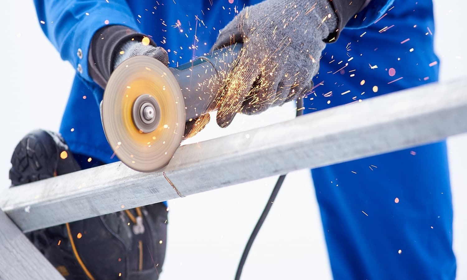 Cropped shot of a technician worker cutting steel on sonstruction site welding constructionist work profession occupation job craft metal metalworking industrial equipment tools.
