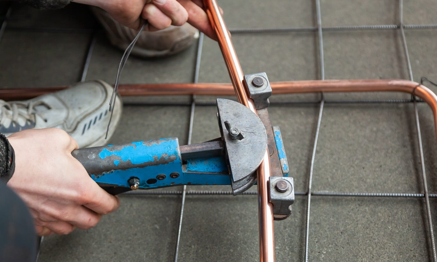 Close-up male hands bends new copper pipes by blue pipe bender, lay pipeline, installation tubes on floor with warm heating of apartment, view from above, horizontal