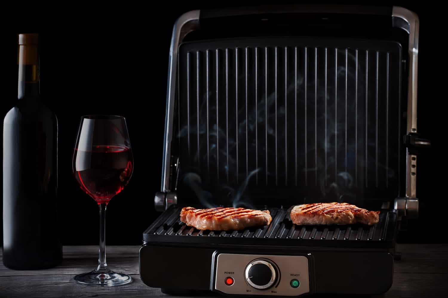 Fried steaming meat with red wine on a wooden table. Black background. Luxury style.