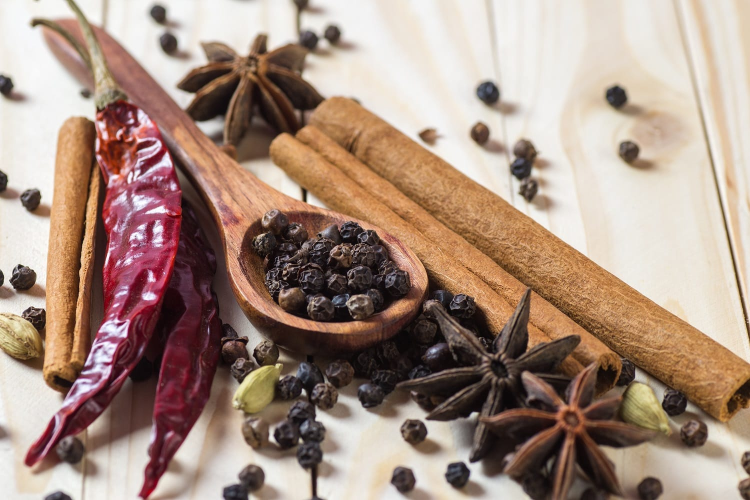spices herbs food cuisine ingredients cinnamon sticks anise stars black peppercorns chili cardamom cloves wooden surface