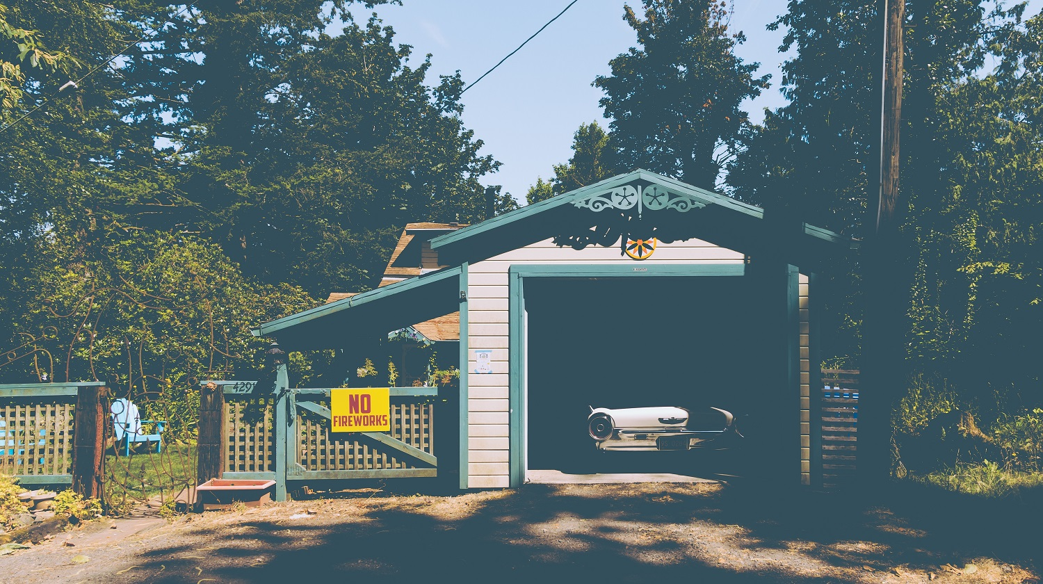 """An old vintage car parked in a small garage next to a sign on a fence that reads """"NO FIREWORKS"""""""