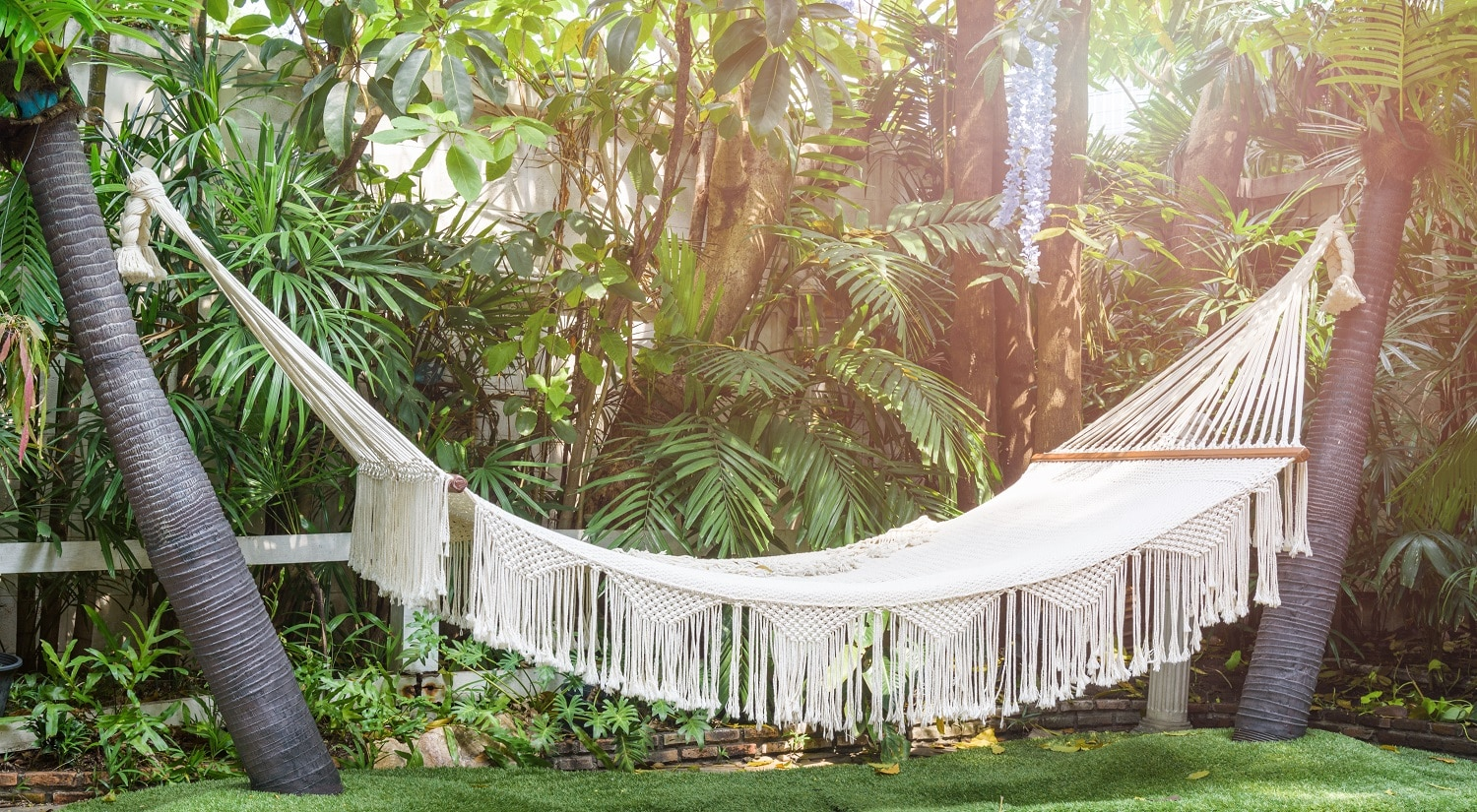 Empty white hammock hanging between palm trees on the garden for recreation or relaxation on summer day