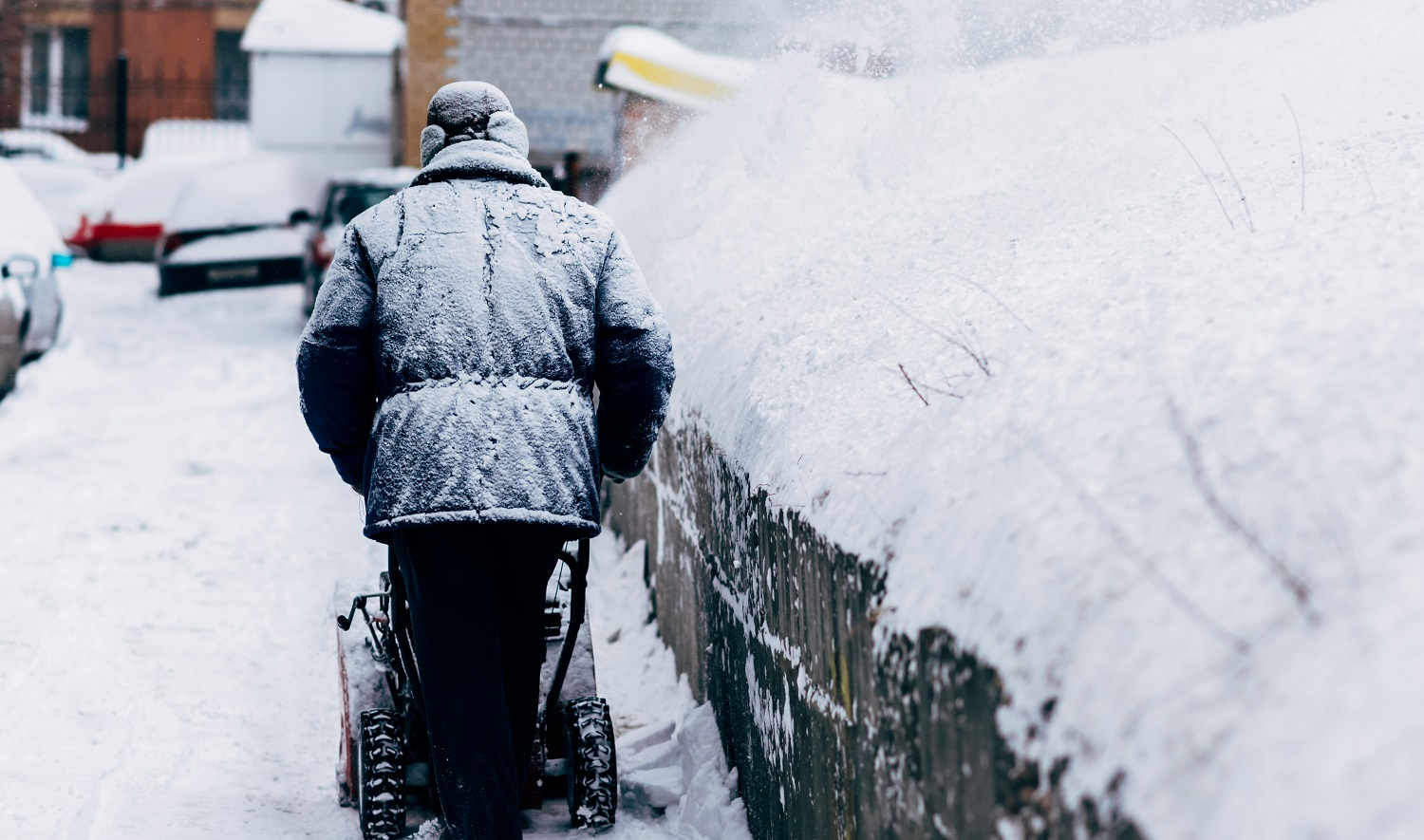 a man cleans up in the yard removes the snowthrower