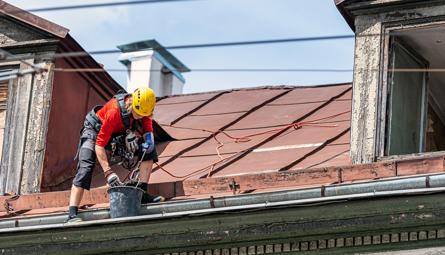 Riga, Latvia- July 3, 2020: Industrial climber removes leaves and dirt from house rooftop rain gutter