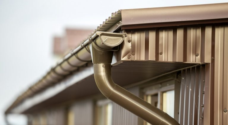 Close-up detail of cottage house corner with metal planks siding and roof with steel gutter rain system. Durability, professional construction, drainage pipes installation and connection concept.