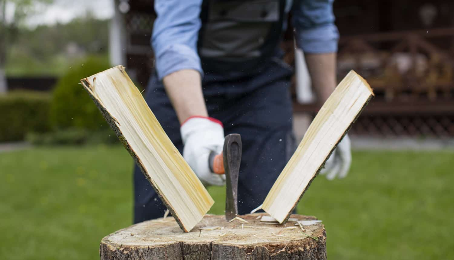 Close up strong man lumberjack in uniform chopping wood with sharp ax on wooden hemp, sawdust fly to sides. Powerful ax blow, woodworking, harvesting wood for winter. Splitting logs with sharp hatchet