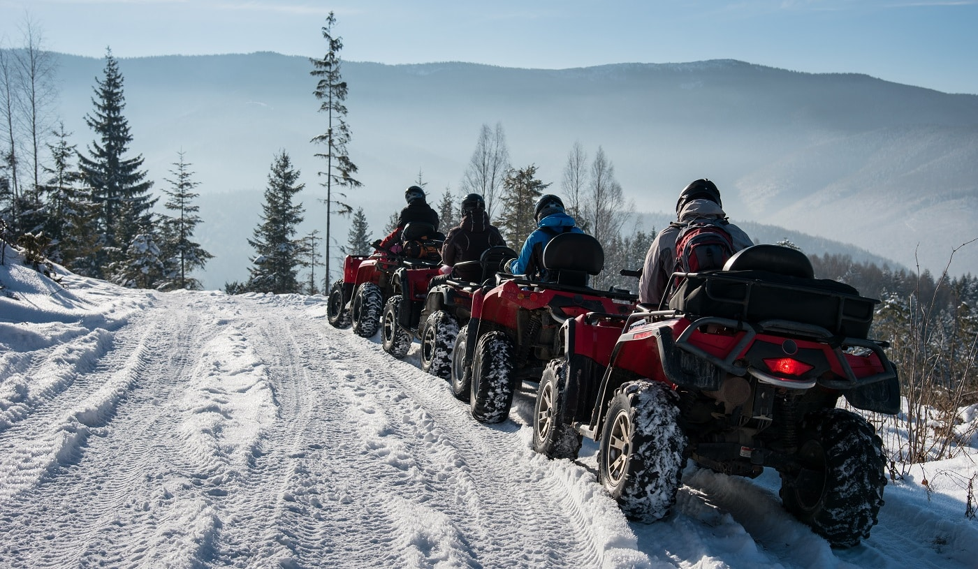 Four ATV riders on off-road quad bikes on snow in the winter mountains