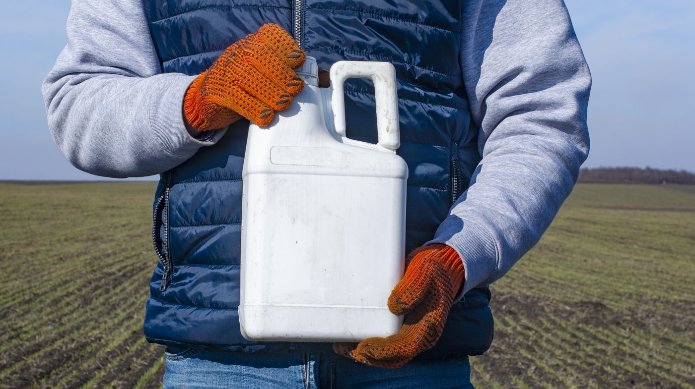 Protection of crops from pests and diseases. Bottle with a pesticide in the hand of an agronomist.