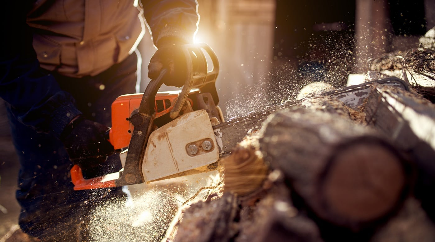 Chainsaw in action cutting wood. Man cutting wood with saw, dust and movements.