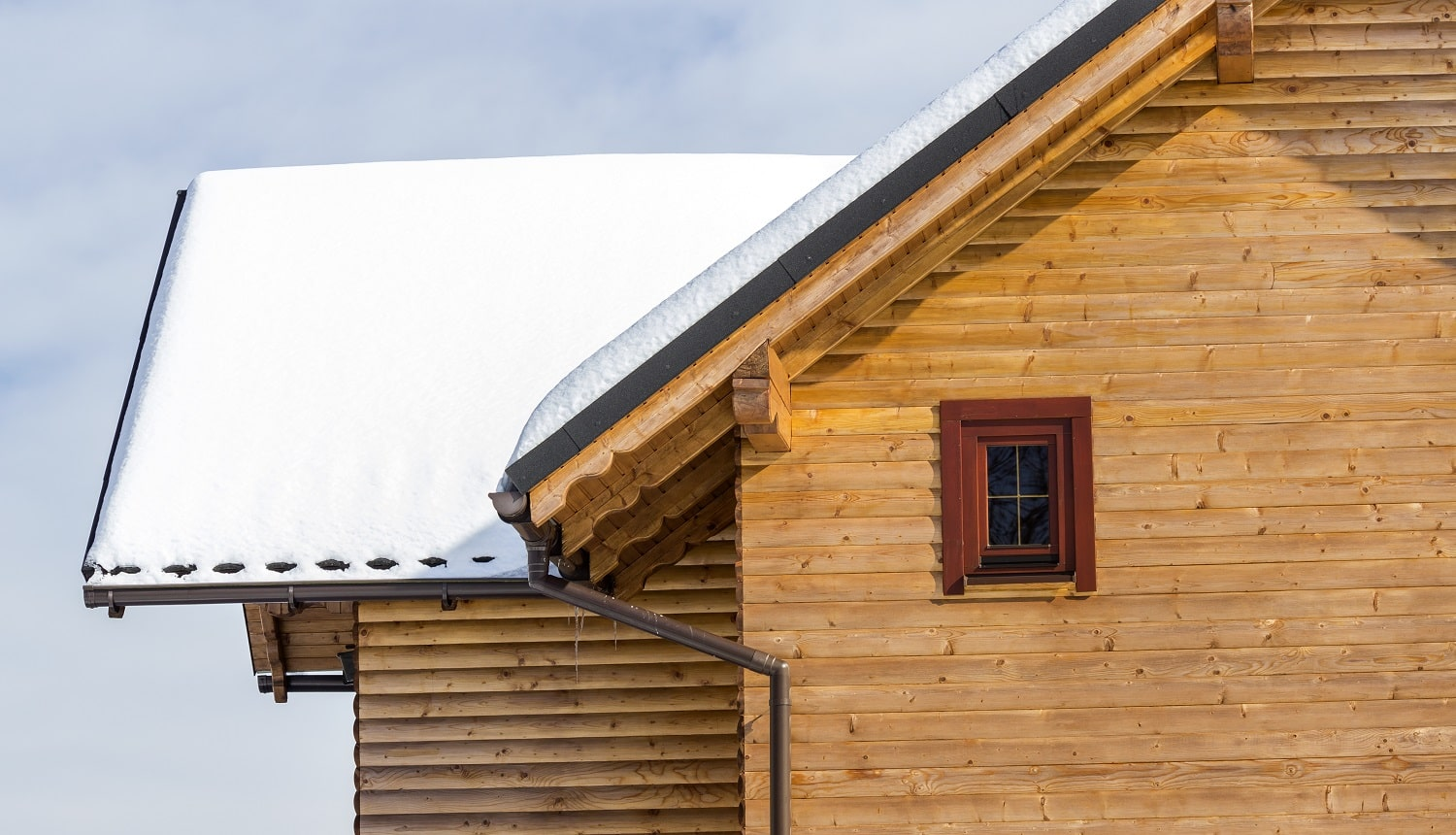 Detail top of wooden ecological traditional cottage of lumber materials with steep roof, attic rooms covered with snow on sunny winter day. Old traditions and modern professional construction concept.