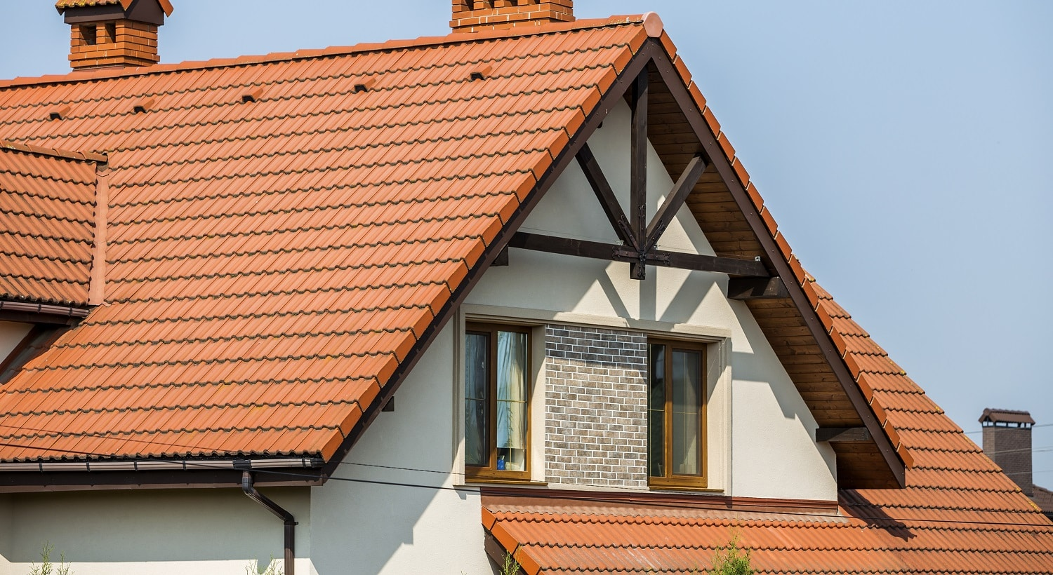 Top of big modern expensive residential house cottage with steep shingled brown roof, high brick chimneys, stucco walls, gutter system and plastic attic windows on blue sky copy space background.