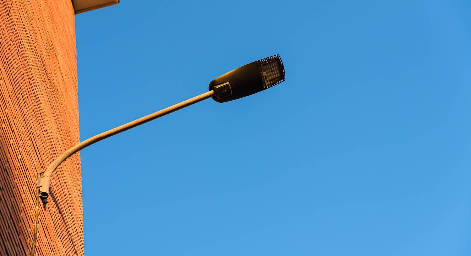 Lamppost on the red wall of a building, by day, with a blue sky background.