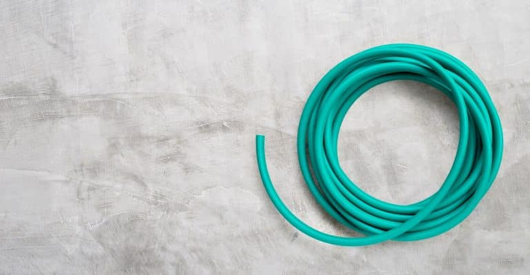 Green garden hose on concrete background. Copy space