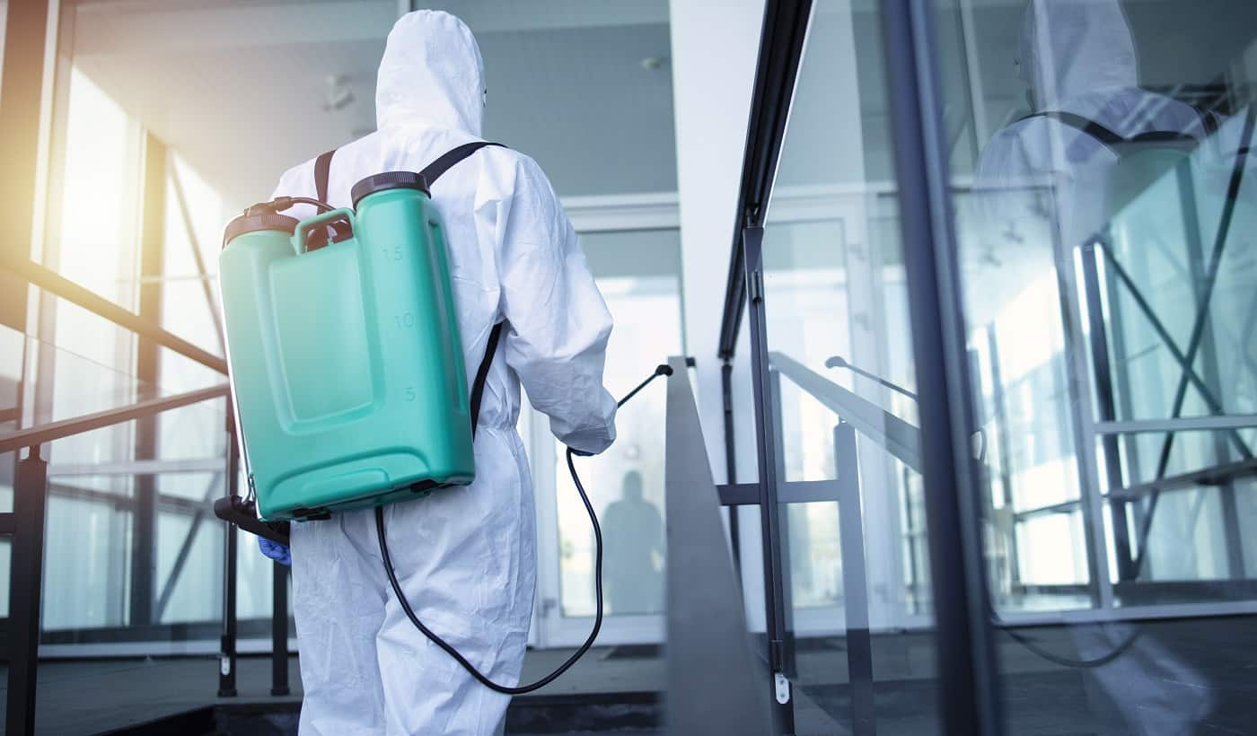 Man with tank reservoir on his back spraying disinfectant to stop corona virus.