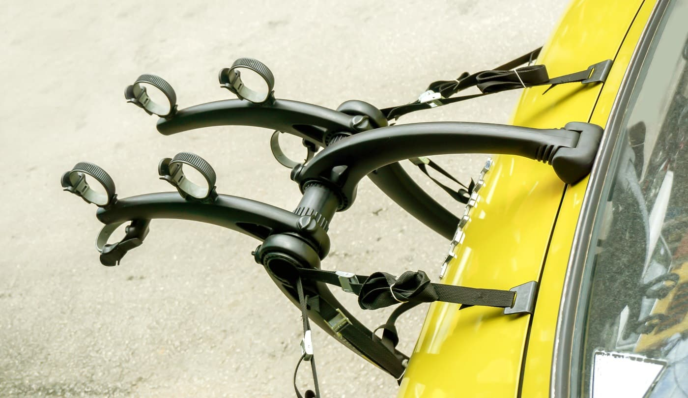 bicycle car holder installation is available on a yellow car trunk.