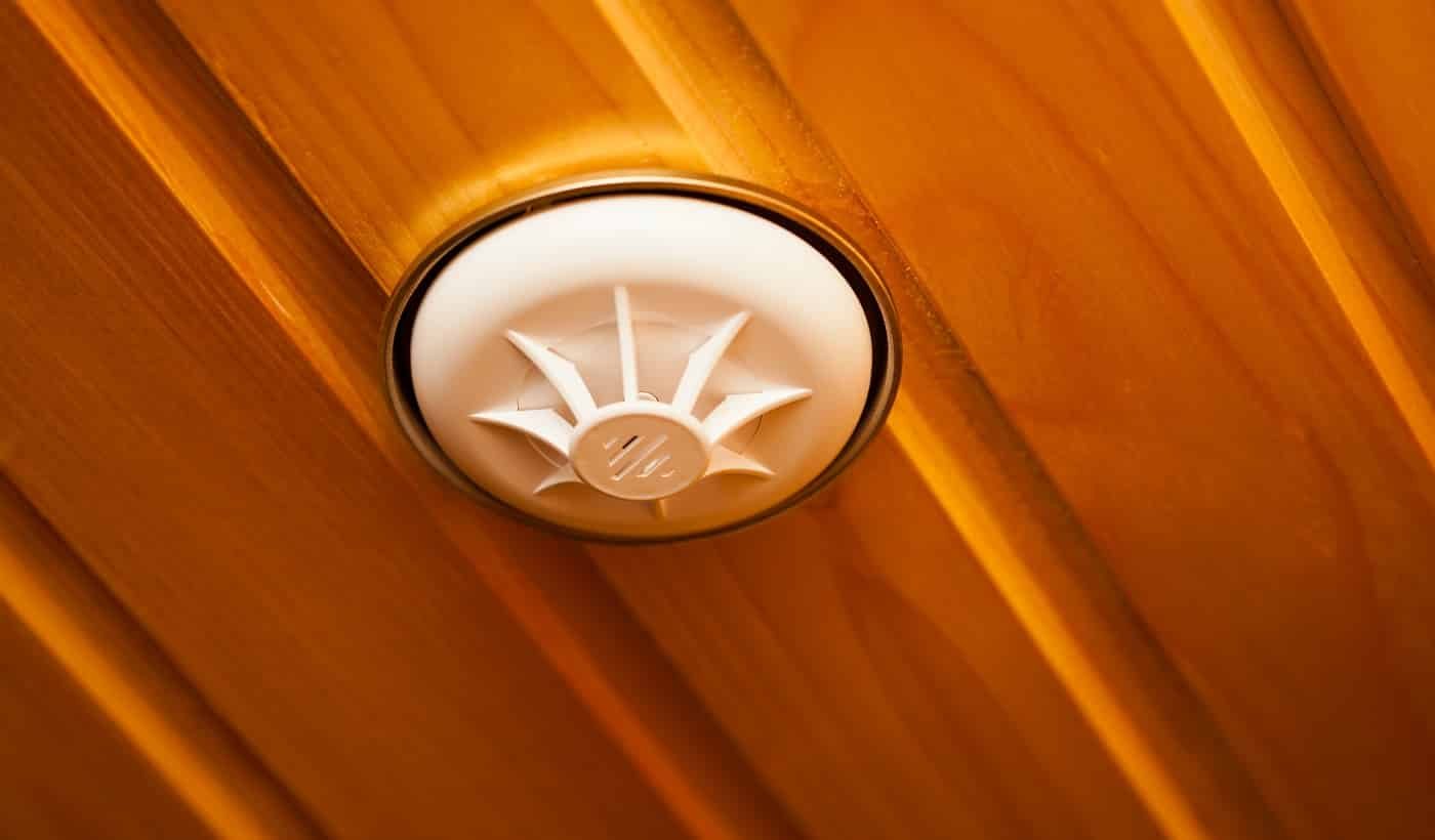 Smoke detector in white plastic case built into wooden ceiling made of glossy panel boards