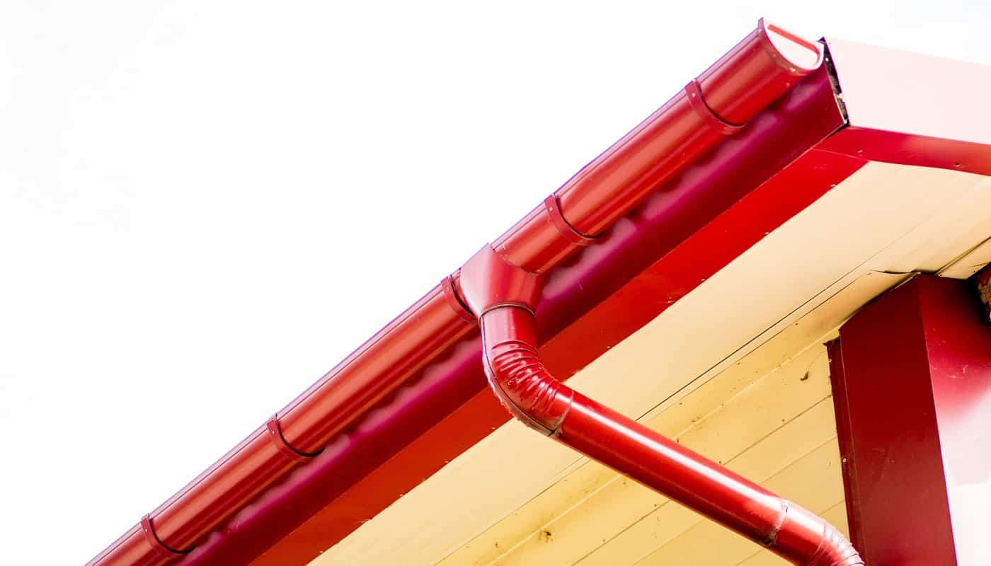 Red gutter on the roof top of house.