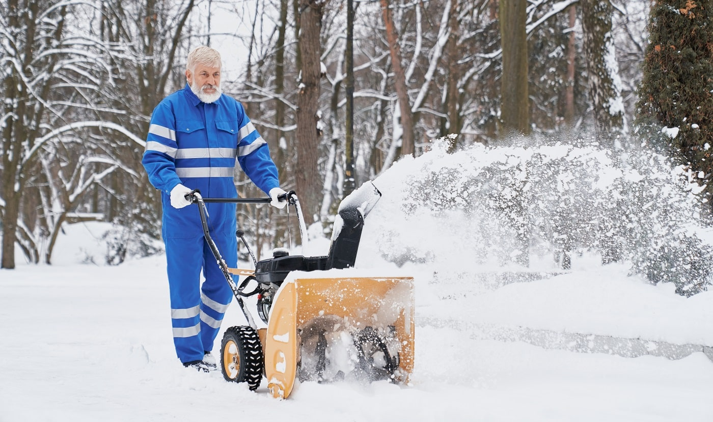 View from side bearded man wearing blue uniform working with snowblower and removing snow from footpath. Elder man keeping machine and driving in park. Concept of city service and maintenance.
