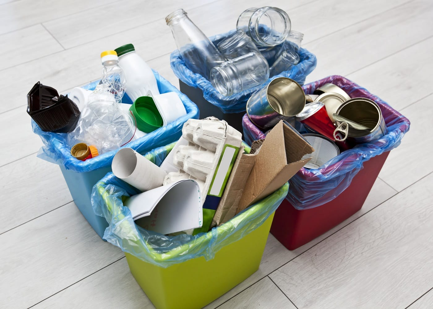 Three different full containers for sorting garbage. For plastic, paper, metal