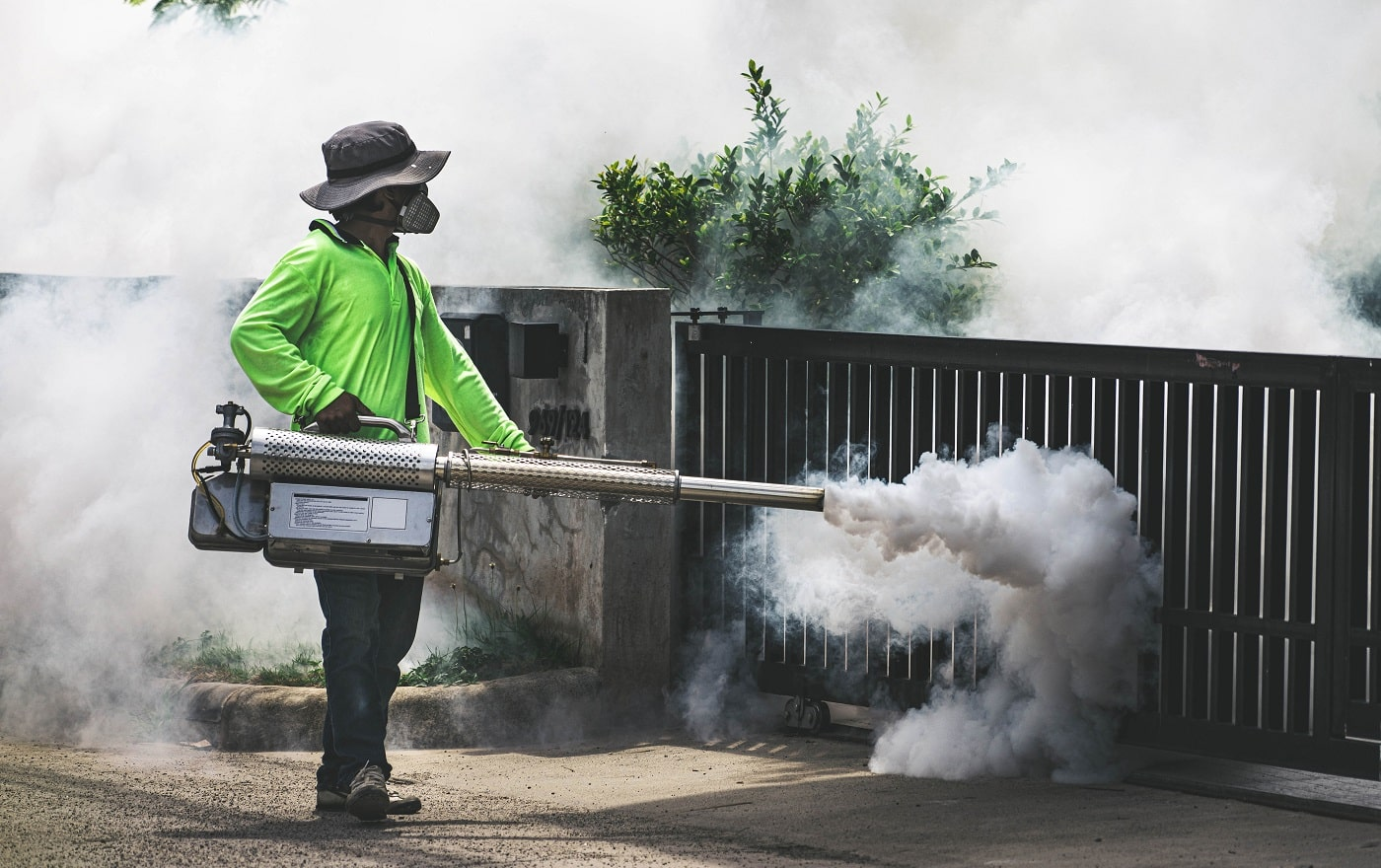 Man using fogger machine to control dangerous from mosquitoes