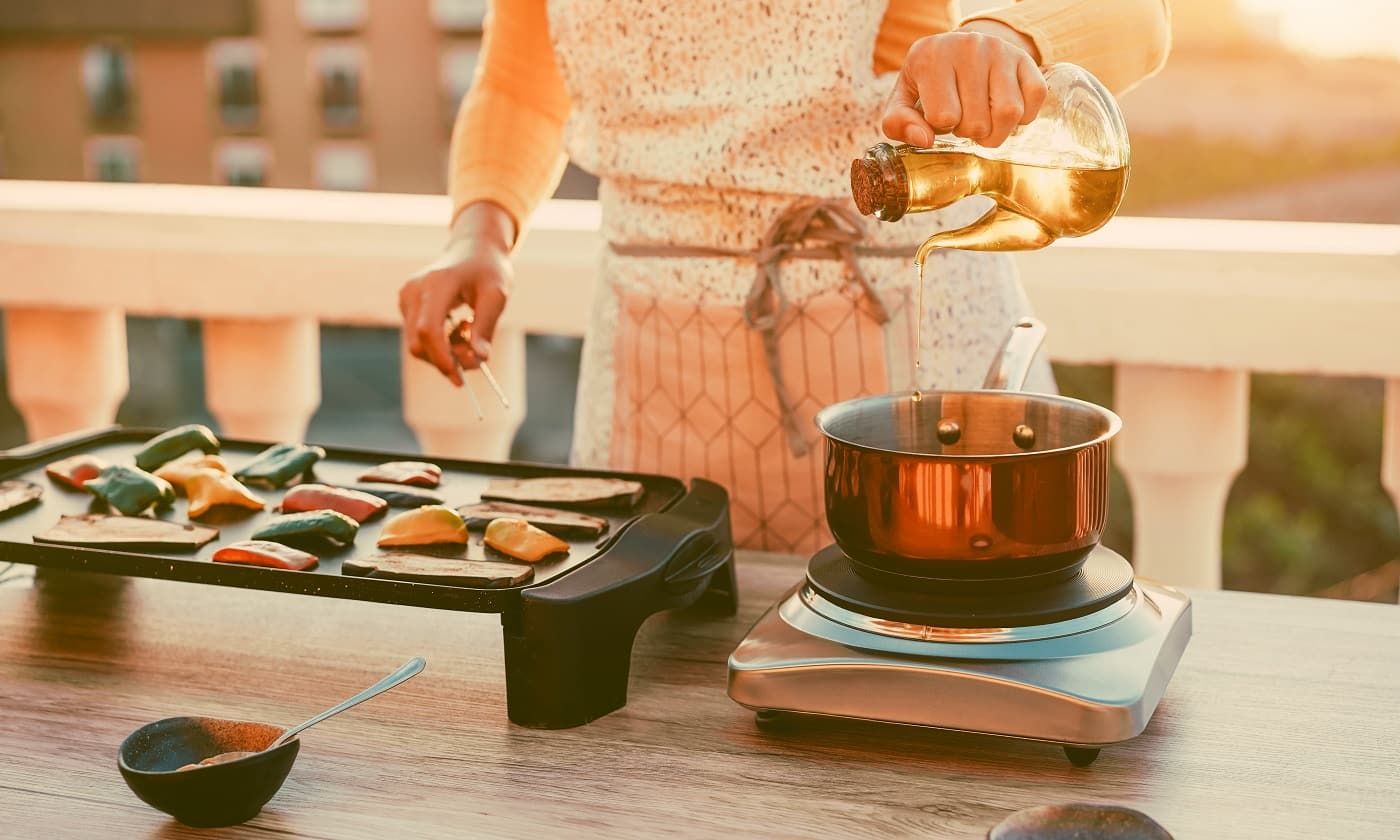 Young woman grill vegetables while preparing dinner in patio terrace outdoor - Food, healthy lifestyle and vegetarian concept - Focus on hand and oil bottle