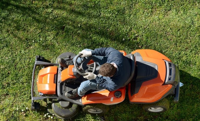 View from above of a man mowing a lawn on an orange ride-on mower as he attends to yard maintenance