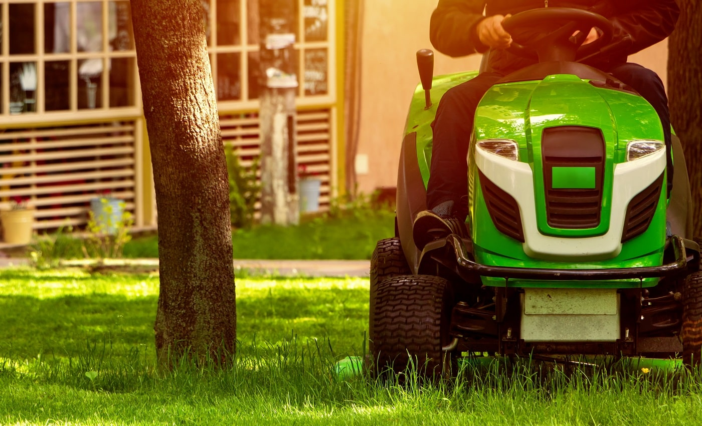 Professional lawn mower mows a green lawn in a park. Gardenning.