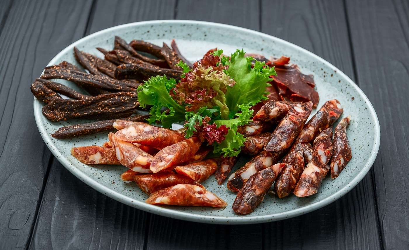 Traditional dry-cured sausage and jerky on a plate. Black background