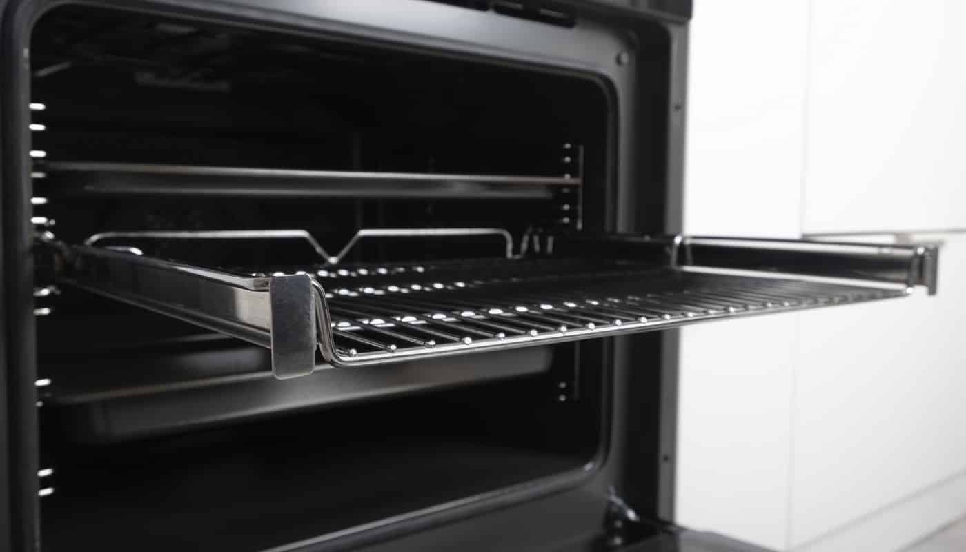 New modern electric oven built in black with screen, convention and grill, empty and open. Telescopic guides. Scandinavian style in a white minimalistic kitchen. High quality photo