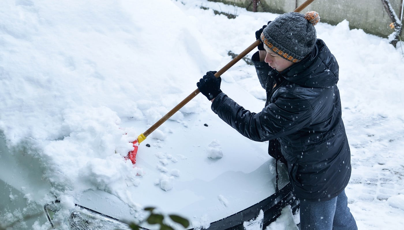 Teenager removing snow with a shovel in the winter