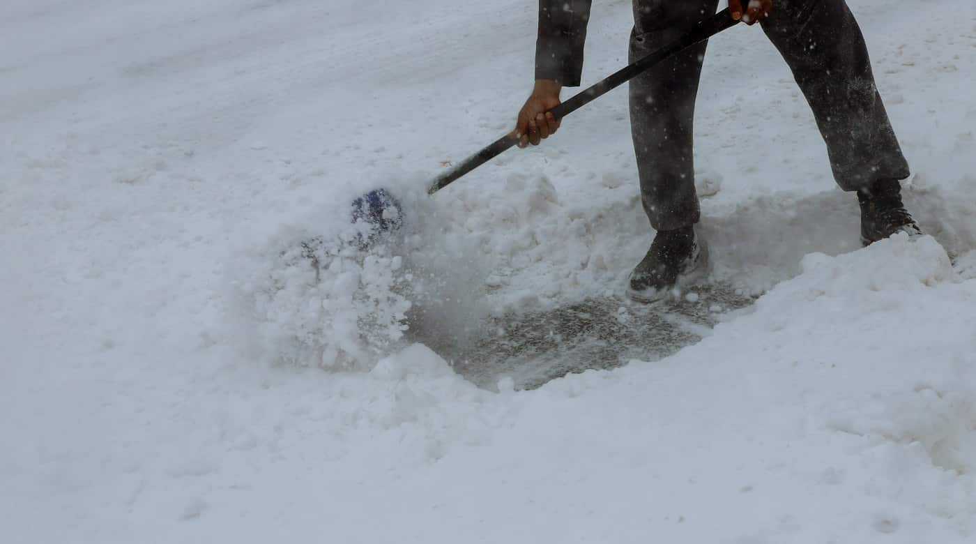Workers sweep snow from road in winter, Cleaning road from snow storm. Man Removing Snow with a Shovel