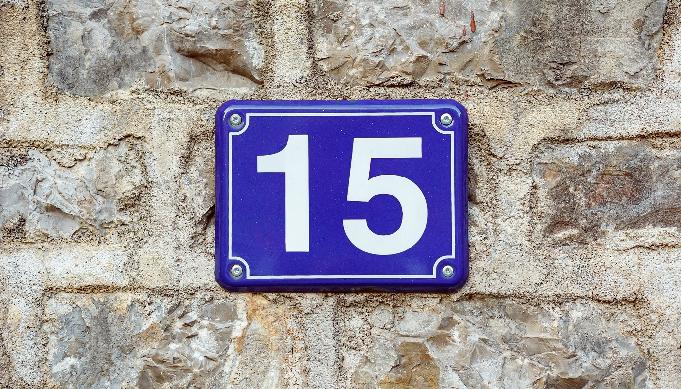 Blue house number fifteen on a stone wall background, closeup