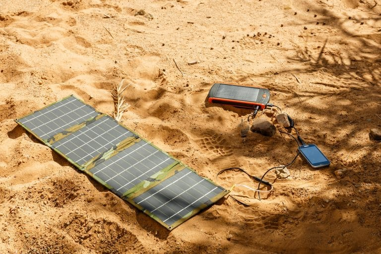 solar panel lying on the ground and charges the smart phone, the Sahara desert. Charge smart phone from the solar battery.