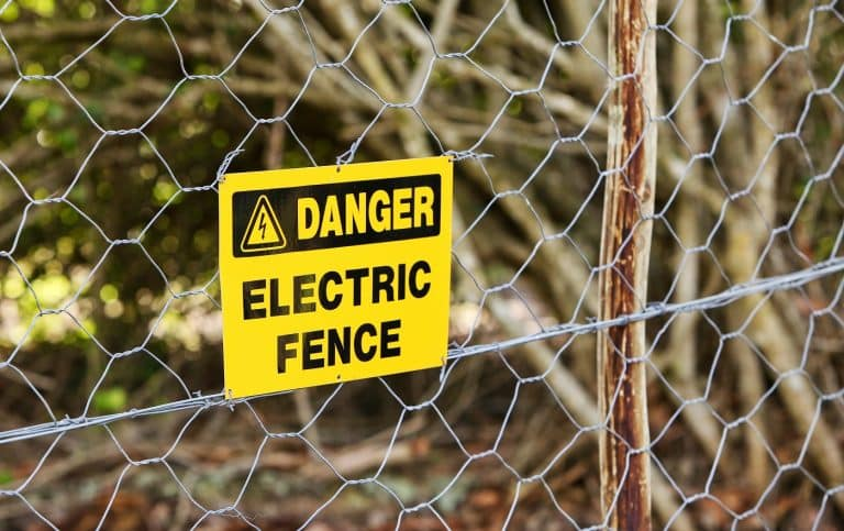 A danger sign hung from the electric fence with the trees in the background