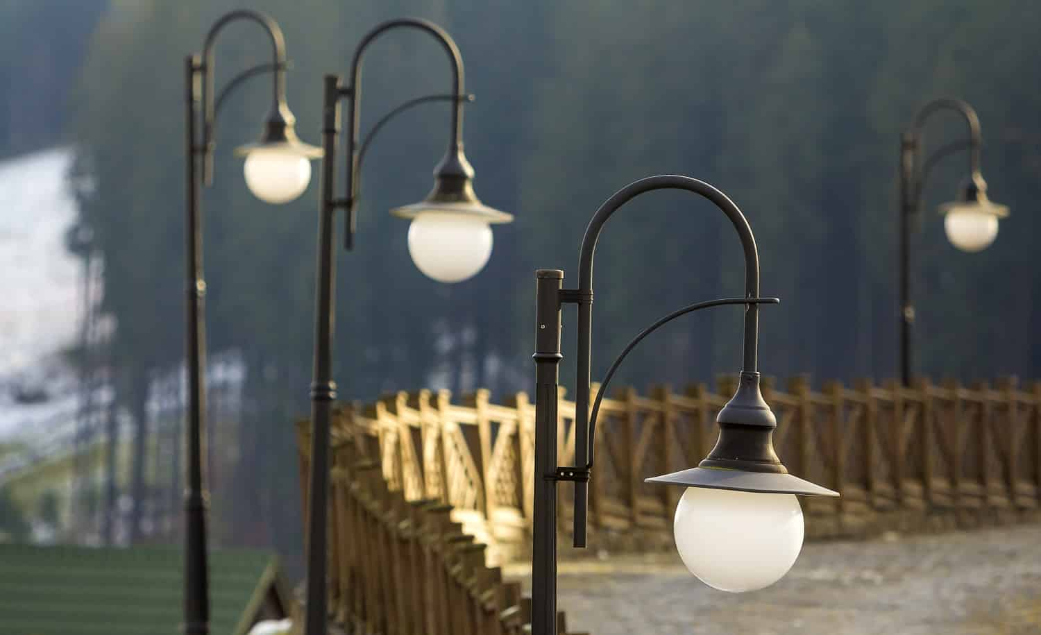 Street light lamps and wooden fence on rural street