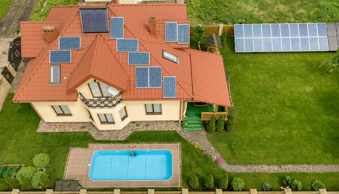 Aerial view of a new autonomous house with solar panels and water heating radiators on the roof and green yard with blue swimming pool.